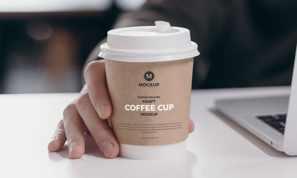 Free-Person-Holding-Kraft-Coffee-Cup-Mockup-Design